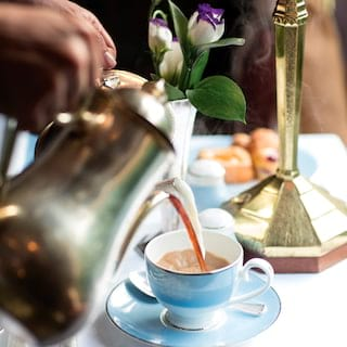 Tea being poured from a silver teapot into a powder-blue teacup with matching saucer