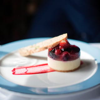 Vanilla panna cotta topped with a summer berry jelly and served with biscotti