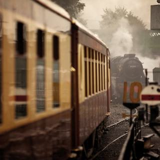 Steam engine and cream and chocolate-coloured vintage train carriages on tracks