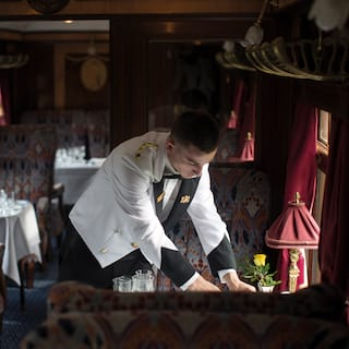 Waiter in a white coat placing silverware on a dining table in a vintage train carriage
