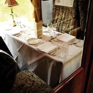 View through a partition window of a formal dining table on a vintage train