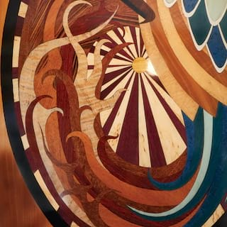 Close-up of a gleaming wood wall panel with an ornate 'sunburst' marquetry design