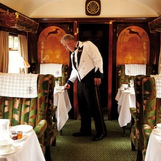Waiter setting a dining table in a vintage train carriage with leaping antelope marquetry