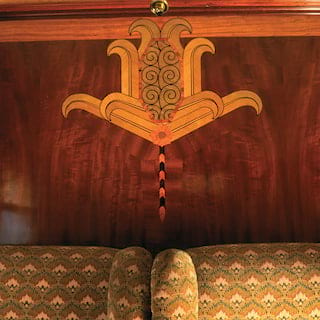 Classical Roman-style design in marquetry on a French-polished wooden wall panel