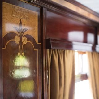 Close-up of gleaming wood panels inside a train carriage with grand marquetry