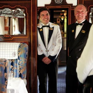 Smiling stewards in formal coats and bow ties in a luxurious vintage train carriage