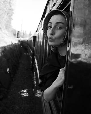 Lady posing from a train carriage window