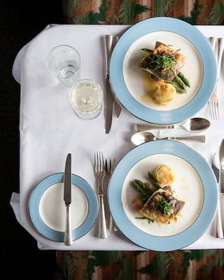Birds-eye-view of two steak and asparagus dishes on powder blue-rimmed plates