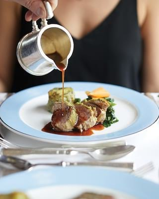 A hand pouring gravy from a silver jug onto a steak dish on a blue-rimmed plate