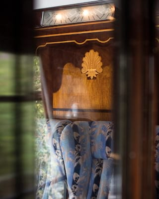 View through a glass partition of a blue-patterned armchair under ornate marquetry