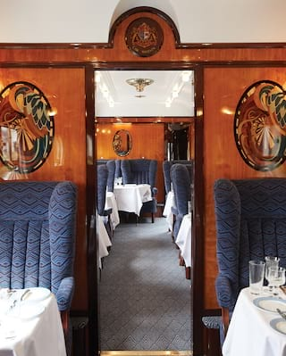 View through the aisle of a vintage train carriage with navy blue armchair seating