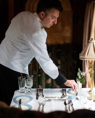 Waiter in a white coat placing silverware on a formal dining table on a train