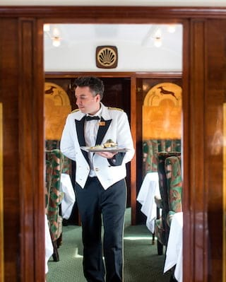 Waiter in a formal white coat holding a silver tray in a vintage train