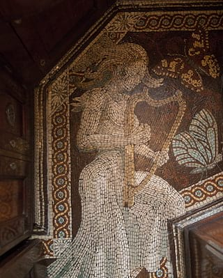 A stunning mosaic tile floor with a design of the goddess Zena playing a harp