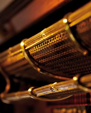 Close-up of a gleaming vintage brass luggage rack