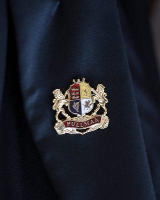 Close-up of a silver lapel badge design of the Belmond British Pullman emblem