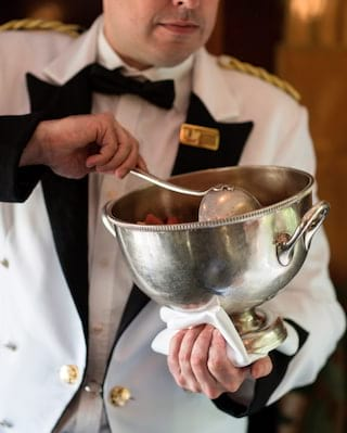 Close-up of a train steward in a white coat ladelling fresh fruit from a silver bowl