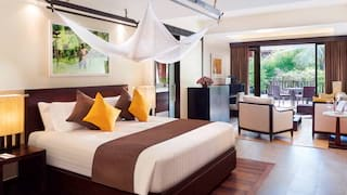 Spacious hotel suite with modern Asian-style decor in yellow and brown hues