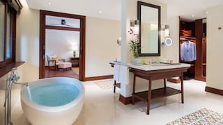 Filled standalone tub in a bright spacious bathroom with dividing feature wall
