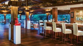 Spacious open-air bar with white leather barstools and polished wooden floors