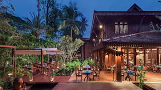 Timber-framed open-air pagoda restaurant terrace dotted with tables and palm plants