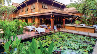 Restaurant terrace overlooking a lily pond beside a timber-framed pagoda