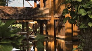 Ornate timber-framed hotel reflected in a shallow moat surrounded by palms