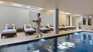 Indoor spa pool in a light spacious room lined with sun beds