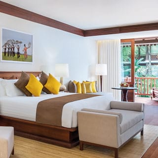 Spacious hotel suite with yellow and tan accents and polished wooden floor