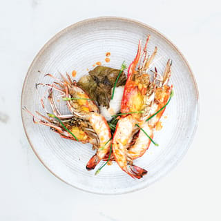 Birds-eye-view of a circular white plate containing a shrimp dish