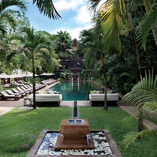 Outdoor pool surrounded by sun beds, parasols and palms, with a fountain in front