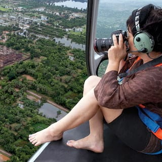 Photographer perching on the edge of a helicopter soaring over Angkor Wat