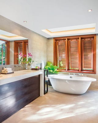 Spacious bathroom with bamboo windows and gleaming standalone bathtub