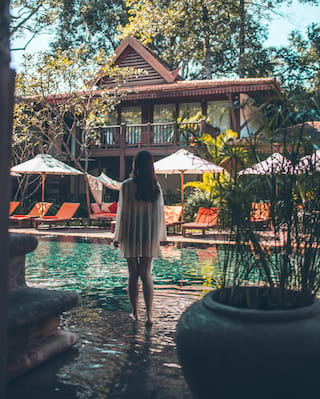 Lady standing in a shallow pool overlooking a grand colonial residence