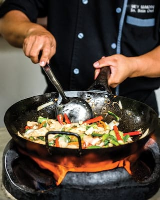Close-up of a chef stirring stir-fry vegetables in a large wok over a fire