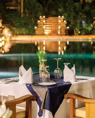 Table for two overlooking a candlelit pool glittering in evening light