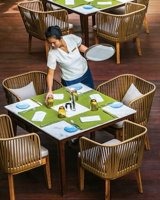 Waitress setting a square green-topped table surrounded by bamboo chairs