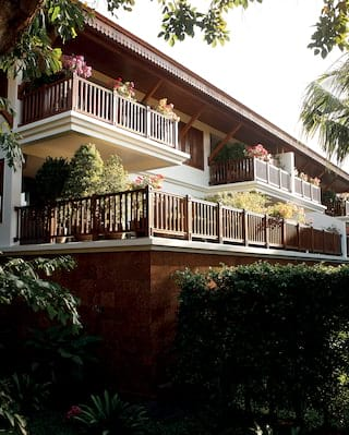 Colonial-style Asian villa with wooden balconies, surrounded by plants and shrubs