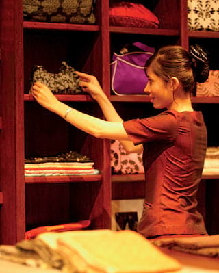 Boutique staff member organising silk items on wooden shelving unit