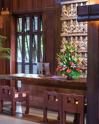 Polished teakwood desk in a cavernous room with a Khmer stone relief on the wall