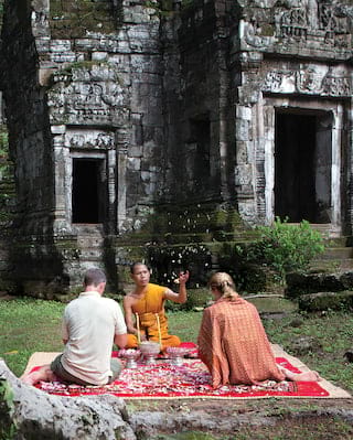 An orange-robed monk sat on a blanket with two tourists in a blessing ceremony
