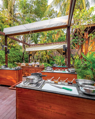 Outdoor cookery school under a teak wood pergola surrounded by lush foliage