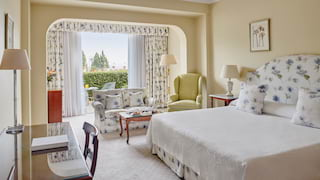 Primrose yellow hotel room with a pillowy king-bed and floral patterned furnishings