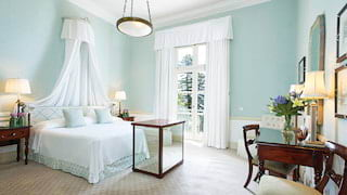 Double-height hotel room with pastel blue walls, mahogany vanity desk and king-bed