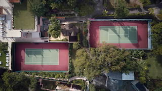 Birds-eye-view of two tennis courts surrounded by lush gardens