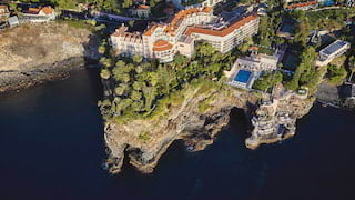 Aerial view of a vast Victorian clifftop hotel with a clay tiled roof and outdoor pool