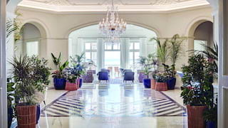 Hotel lobby with indigo blue armchairs and marble floors under a crystal chandelier