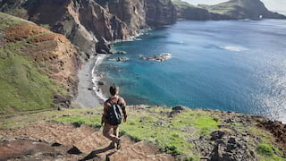 Man with a backpack descending stone steps on a coastal path overlooking the ocean