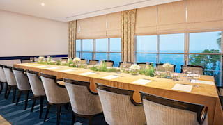Boardroom table set for a meeting in a light and airy meeting room with sea views