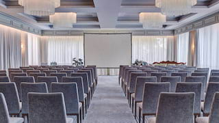 Grey velvet chairs in rows facing a projector screen at the far end of an event room